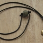 Pendant with dark brown, round leather cord<br>Secured with bead